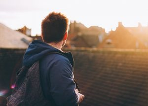 young-man-wearing-backpack-looking-over-houses