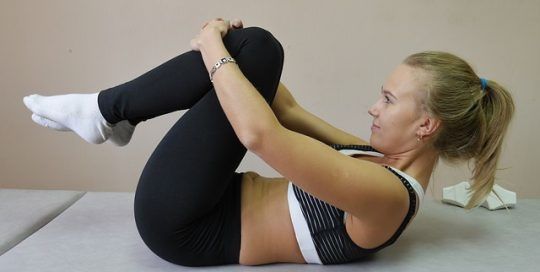 fit-wonan-lying-on-back-doing-stretches