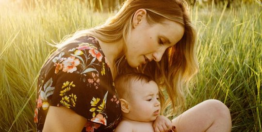 young-mother-and-baby-sitting-in-green-field