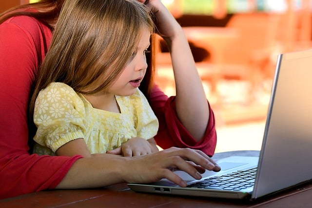 young-girl-sitting-on-mother's-lap-at-computer