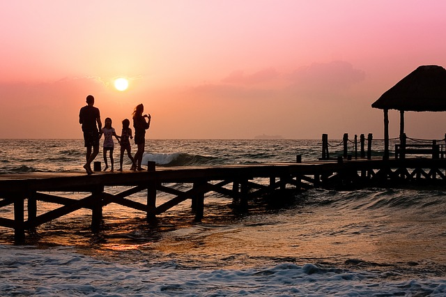 happy-family-holidays-on-pier-at-sunset