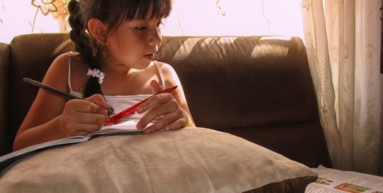 young-girl-sitting-on-lounge-reading